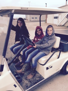 The girls having fun riding around in the old golf cart.